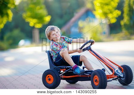 Active little kid boy driving pedal race car in summer garden, outdoors. child racing with fast speed and having fun.