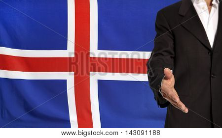 Businessman with an open hand waiting for a handshake concept for business with the Iceland flag in the background