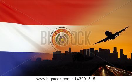 Travel and transport concept with skyline silhouette highway traffic and airplane at sunset merged with real fabric flag of Paraguay