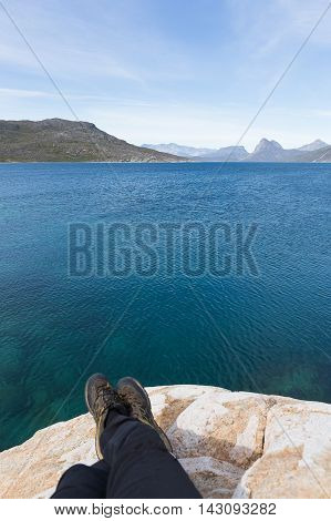 Traveler by sit on stone put feet above the deep blue sea happy travel and relax travel concept.