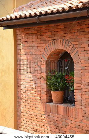 Shady brick facade with a pot of plant