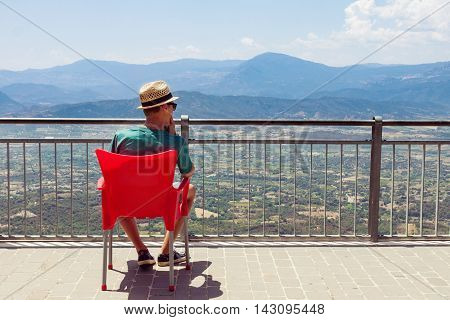 Teenager sitting on red chair and looking at the mountainous view in Sardinia Italy. Picture with copy space on the right