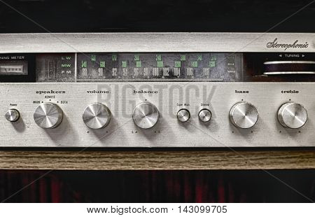 Old dusty Hi-Fi receiver with radio dial and silver buttons