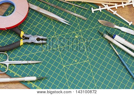 Plastic model kit and tools hobby workplace background top view.