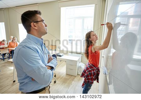 education, school, learning and people concept - student girl writing something on blank white board and teacher in classroom