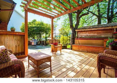 Backyard Deck With Wicker Furniture And Pergola.