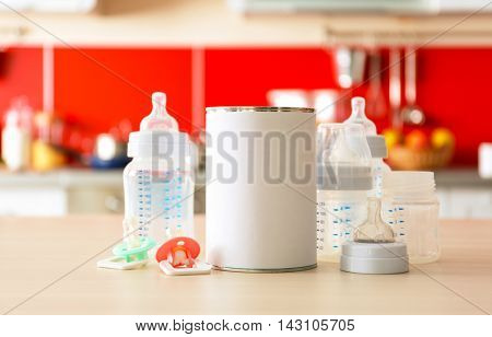 Feeding bottles with bank of baby milk formula on kitchen background