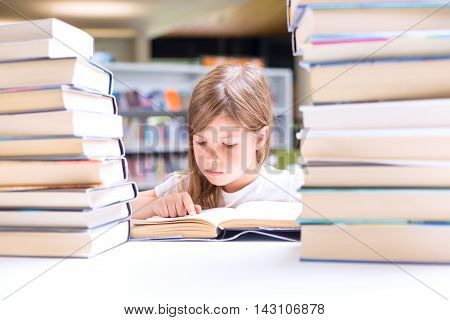 Little Girl Reads A Book Surrounded With Piles Of Books In Library