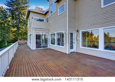 Two Story House With Wooden Walkout Deck Overlooking Backyard Garden.