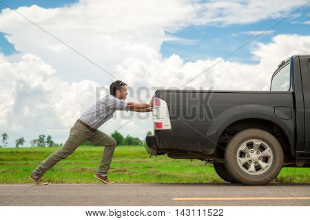 Man pushing a broken car down the road