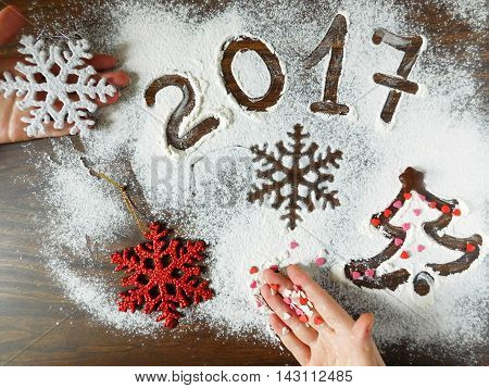 New Year composition made of flour, christmas decorations and confectionery sprinkling lying on a kitchen table . New year symbols.
