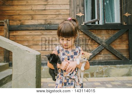 girl playing with kittens on a bench.