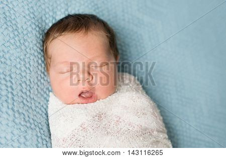 sweet wrapped newborn baby sleeping with open mouth on blue blanket