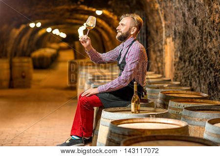 Handsome sommelier in apron and checkered shirt looking at wine glass sitting on the barrel in the old cellar.