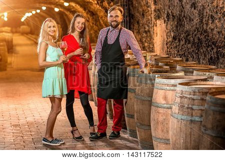 Wine degustation with sommelier or wine maker and two pretty women in colorful dresses in the old cellar.