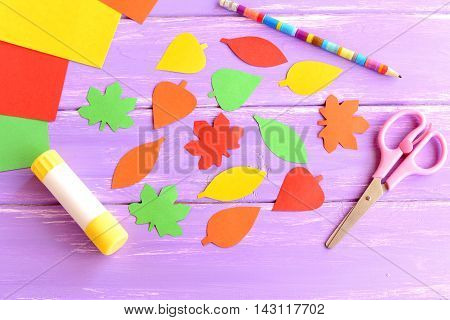 Colorful leaves cut from colored paper, scissors, glue stick, pencil, paper sheets on purple wooden background. Children activity concept. Easy autumn crafts. Kindergarten crafts background. Top view