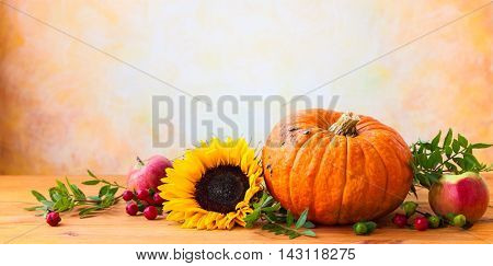 Autumn concept with flowers,pumpkin and seasonal fruits