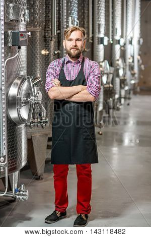 Portrait of a handsome wine maker in working apron at the manufacture with metal tanks for wine fermentation. Wine production at the modern factory