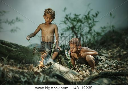 The children helped blow the fire to roast their fish life in the countryside.