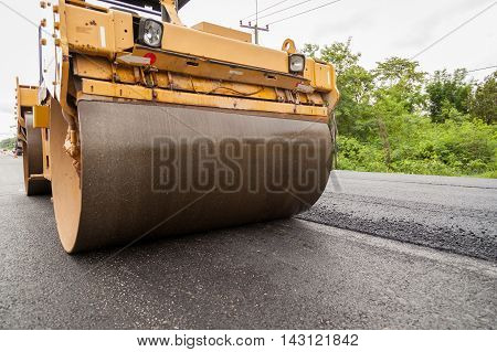 Road construction works with roller compactor machine and asphalt finisher