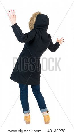 Back view woman in winter jacket  Balances waving his arms.   Standing young girl in parka. Rear view people collection.  backside view of person.  Isolated over white background. The girl in warm