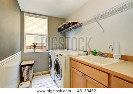 Laundry Room With Wood Cabinets And Tile Floor.