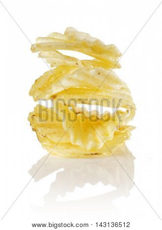 Unflavored ridged potato chips stacked on a reflective background.
