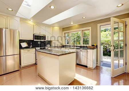 White Kitchen With Granite Tops. Kitchen Island And Tile Floor.
