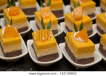 A cut mini orang cheese cake in mni white cup
