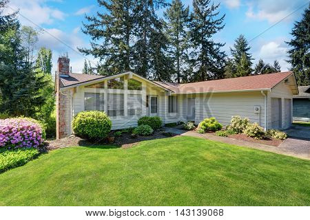 American House With Siding Trim And Well Kept Lawn Around.