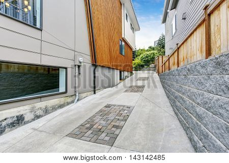 Luxury Driveway To Garage Near Modern House With Wooden Pannel Trim.