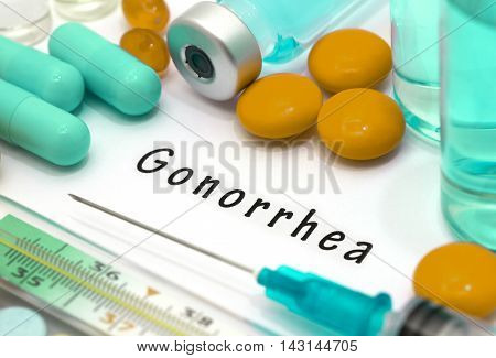Gonorrhea - diagnosis written on a white piece of paper. Syringe and vaccine with drugs.