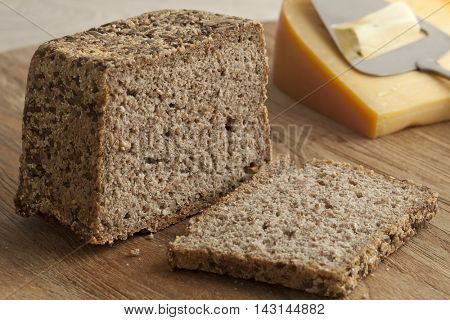 Piece of homemade fresh baked rye bread and cheese in the background