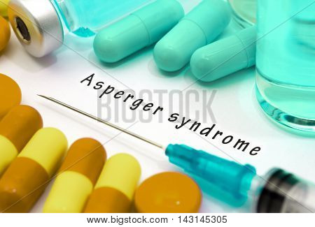 Asperger syndrome - diagnosis written on a white piece of paper. Syringe and vaccine with drugs.