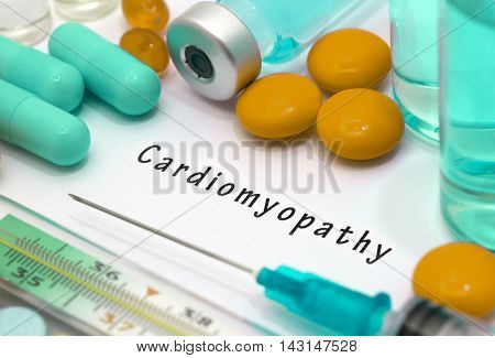 Cardiomyopathy - diagnosis written on a white piece of paper. Syringe and vaccine with drugs.