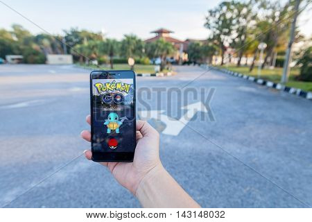 California, United States - July 30, 2016: Close up view of a person hand holding a smartphone and playing Pokémon Go