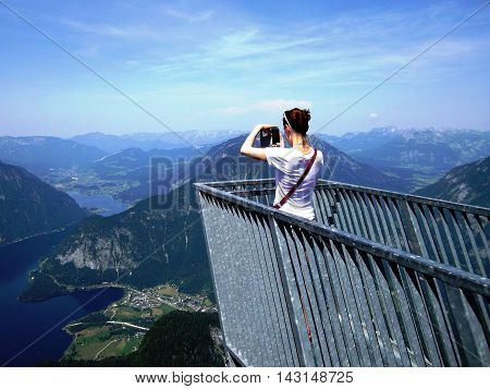 Young girl standing on the viewing platform Five Fingers and taking photos with view of Alps and lake Hallstatter see, Dachstein, Salzkammergut region, Upper Austria, Austria