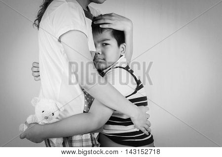 Little boy sad in hugging of mother
