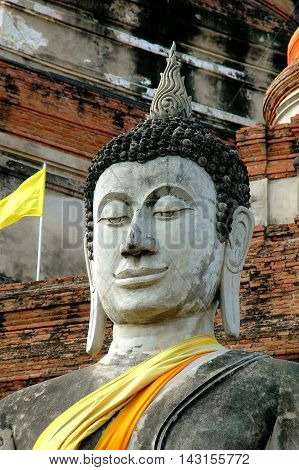 Ayutthaya Thaland - December 28 2005: An immense seated Buddha in front of the great brick Chedi at Wat Yai Chai Mongkhon