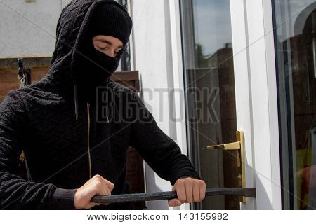 Burglar breaking and entering a suburban house