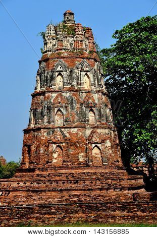 Ayutthaya Thailand - December 20 2010: Ruins of an ornate brick Chedi with indented niches that formerly held Buddha figures at Royal Wat Mahathat