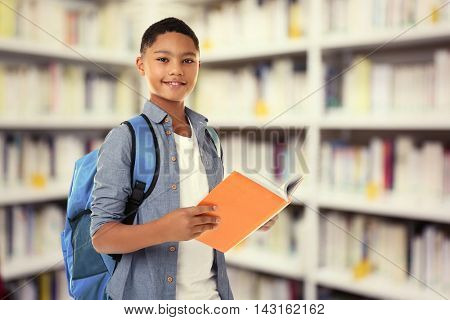 Cute boy with backpack holding book on blurred book shelves background. Library concept.