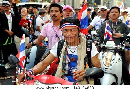 Bangkok Thailand - January 13 2014: Thais on motorcycles riding along Thanon Ratchadamri during the anti-government protest Operation Shut Down Bangkok