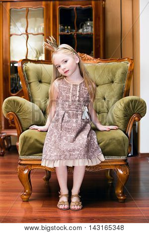 The Little princess on a chair with crown