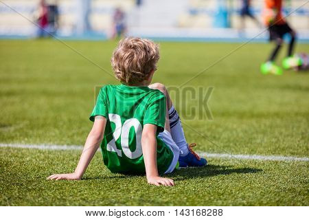 Youth Soccer; Little Soccer Player. Young Boy as a Soccer Player Sitting on Football Field and Watching School Soccer Match