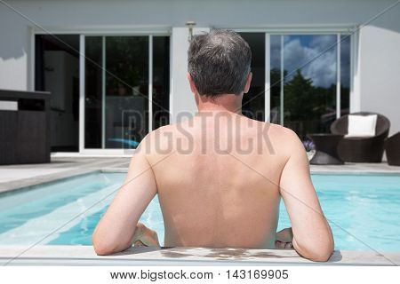 Happy new property owner in front of his house in a pool