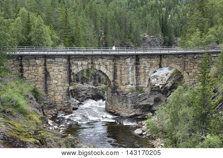 Old stone bridge over a mountin stream in the North of Norway.
