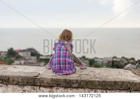 Child girl sitting on the parapet with his back to the camera and looking at the sea
