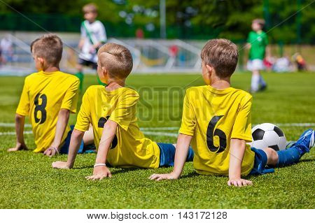 Young boy player waiting for a kick ball. Young boys in soccer team sitting together on the sports field. Kids as a reserve soccer football players. Football soccer match tournament for children teams.