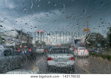 Driving in rain , warning raindrops on glass car  be careful when driving in rainy road